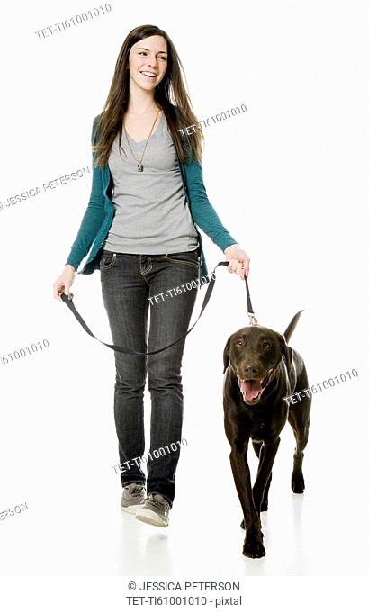 Studio shot of young woman with chocolate labrador