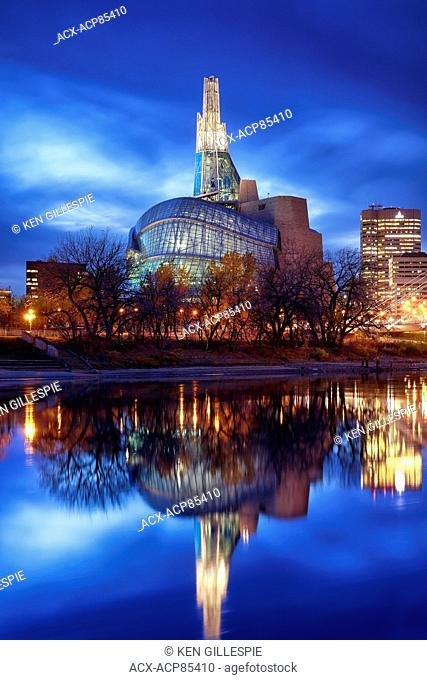 Canadian Museum for Human Rights reflected in the Red River at night, Winnipeg, Manitoba, Canada