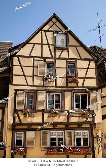 Half-timbered house with stork figures in the historic centre, Colmar, Alsace, France