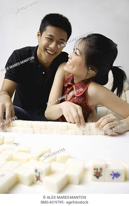 Couple arranging mahjong tiles, smiling
