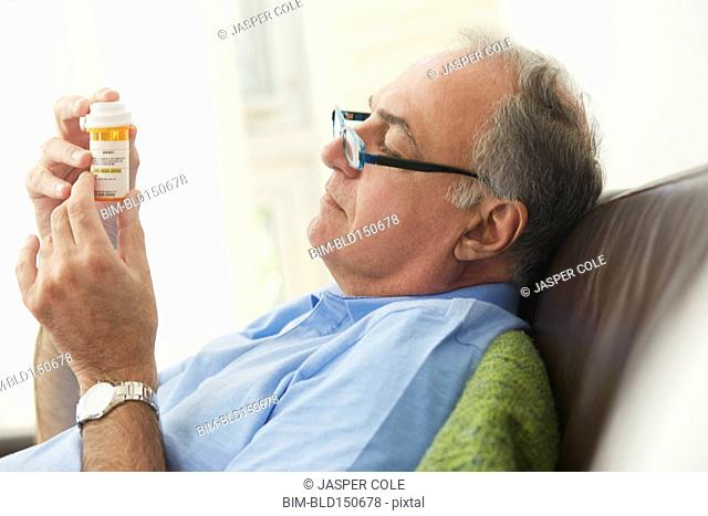 Hispanic man reading prescription medication bottle