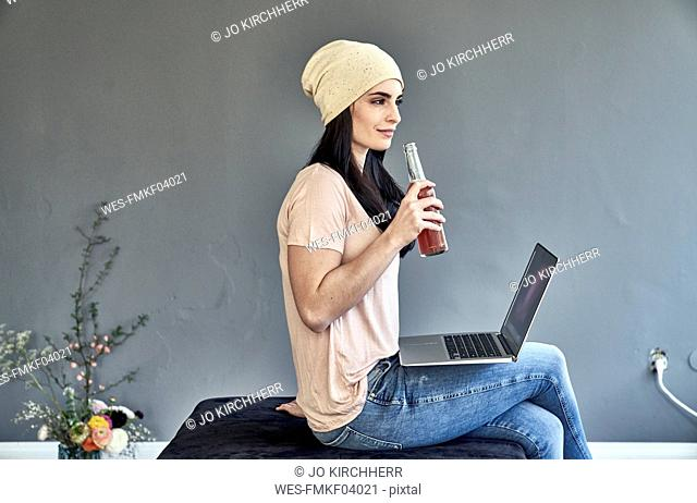 Young woman with laptop holding bottle