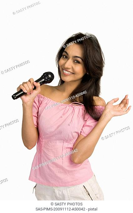 Portrait of a woman singing into a microphone