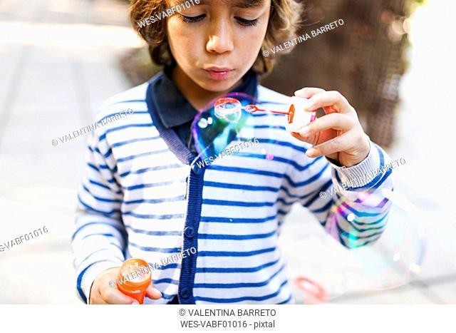 Boy makining soap bubbles in park