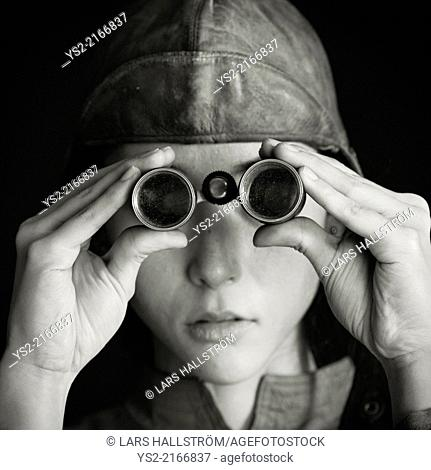 Nostalgic retro styled portrait of serious woman with old fashioned binoculars