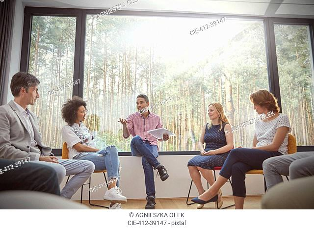 Male therapist with clipboard leading group therapy session