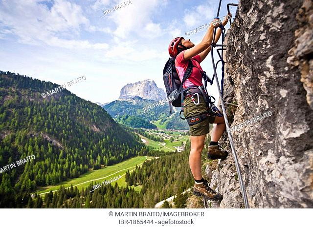 Climber ascending a via ferrata on Stevia Mountain in front of Langkofel and Wolkenstein Mountains in Val Gardena, Puez-Odle Nature Park, Dolomites, Alto Adige