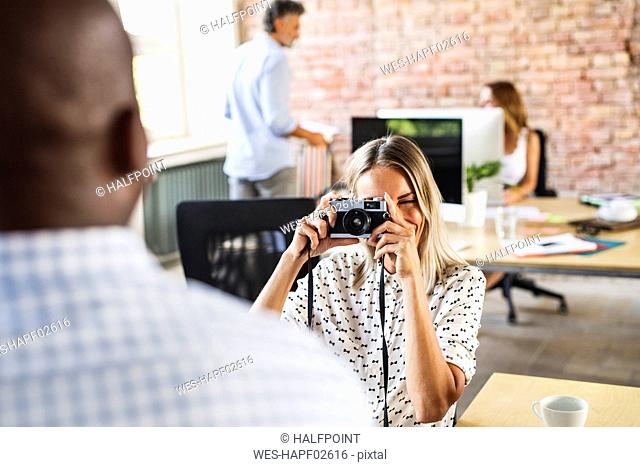Businesswoman with camera taking picture of colleague in office