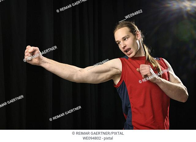 Young male with long hair practicing a swivel Karate punch while yelling in spotlight
