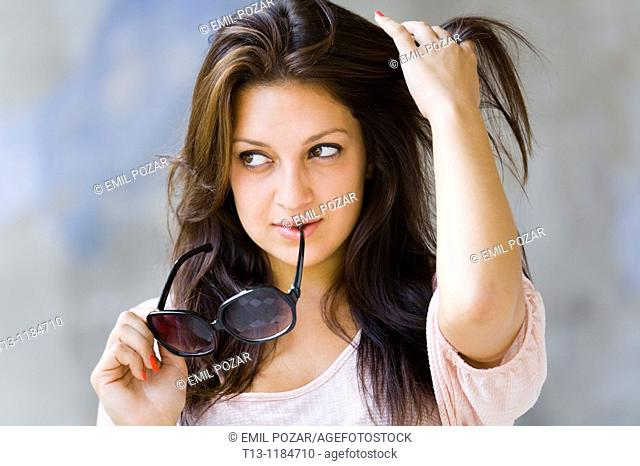 Watching away with sunglasses in hands young woman