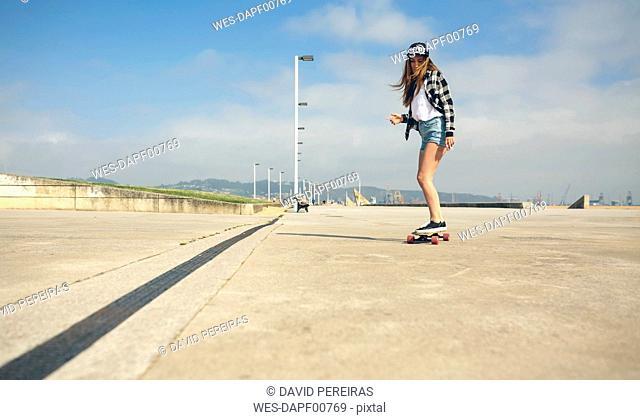 Young woman longboarding on beach promenade