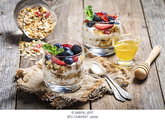 Homemade yogurt with baked granola and berries in small glasses on wooden background