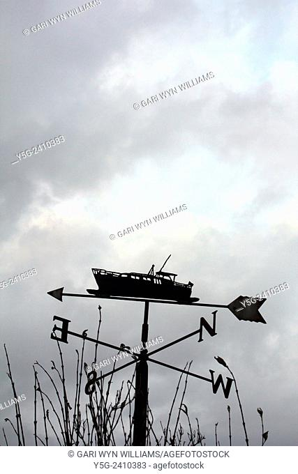 Weather wind spire with boat design and dark sky in wales