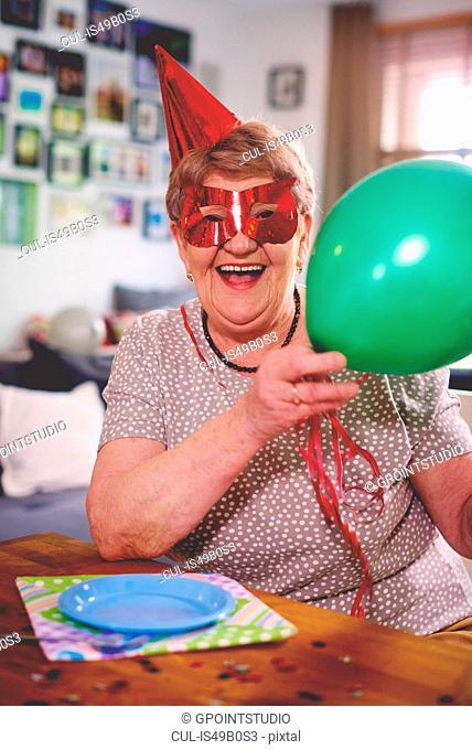 Senior woman waving balloons at birthday party