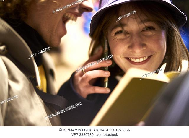 Couple with book and phone. Nightlife, in Berlin, Germany