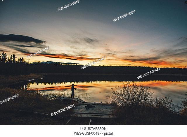 Canada, British Columbia, man fishing at Duhu Lake at sunset