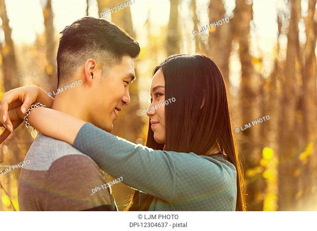 A young Asian couple enjoying a romantic time together outdoors in a park in autumn and embracing each other in the warmth of the sunlight during the early...