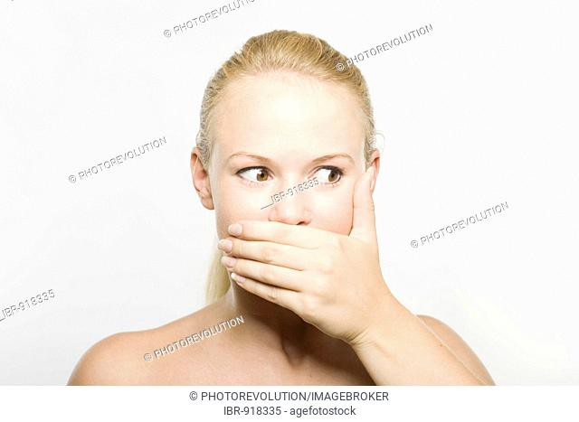Young blonde woman covering her mouth with her hand