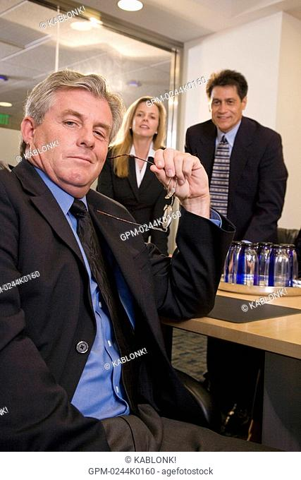 Three multi-ethnic businesspeople in boardroom, focus on man in foreground
