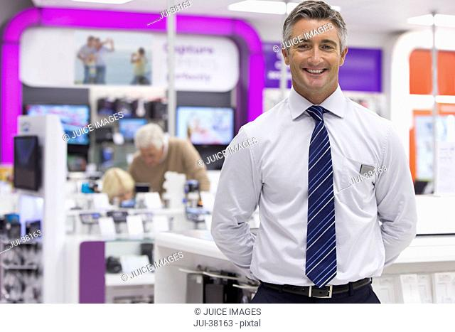 Portrait of smiling salesman in electronics store