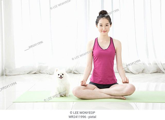 Young smiling woman doing yoga in lotus position with her pet dog