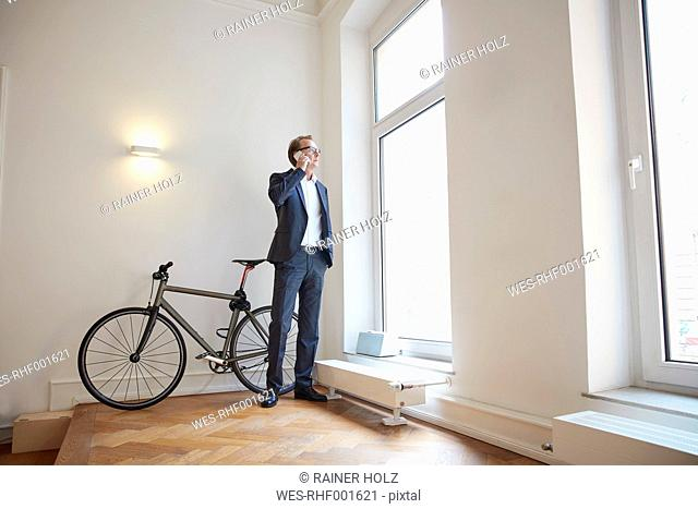 Businessman telephoning with smartphone while looking through window