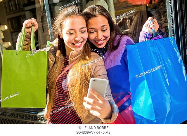 Young female adult twins in city taking smartphone selfie with shopping bags
