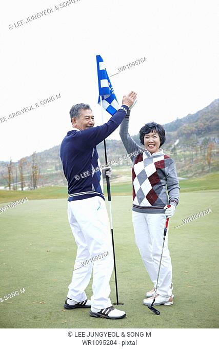 middle aged couple holding a flag on golf field