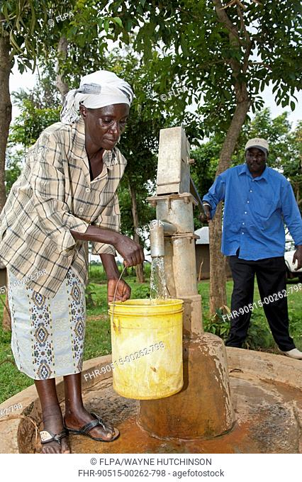 Woman filling bucket with clear water at hand pump well in village, Kenya, June