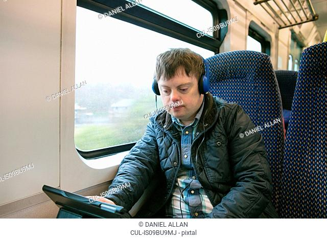 Man with down syndrome using headphones and digital tablet on train