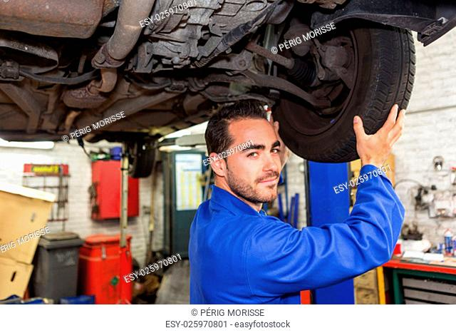 View of a Young attractive mechanic working on a car at the garage