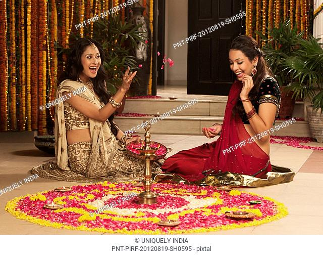 Female friends playing with flowers on Diwali