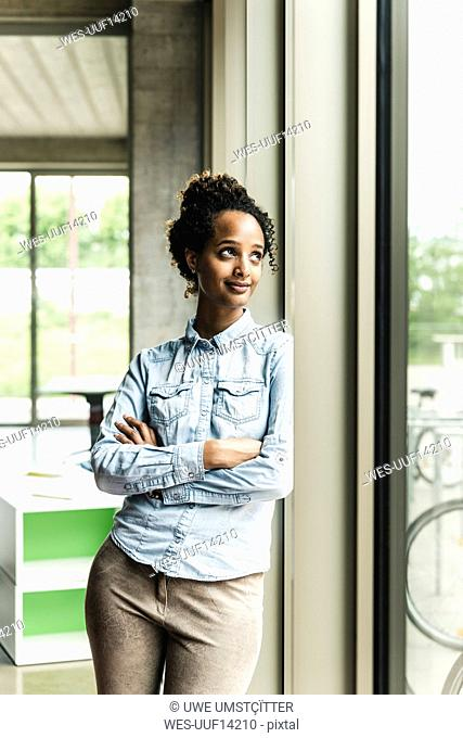 Confident young businesswoman leaning on window in modern office