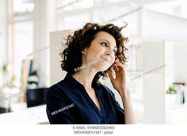 Businesswoman in office thinking and smiling