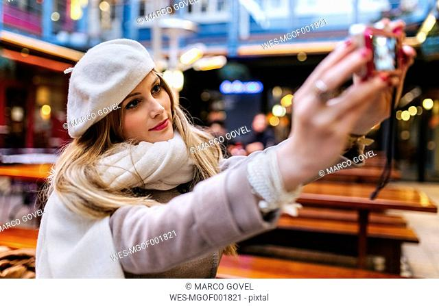 Young woman wearing beret taking selfie with digital camera