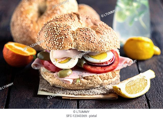 A bagel sandwich with turkey breast, tomato and egg