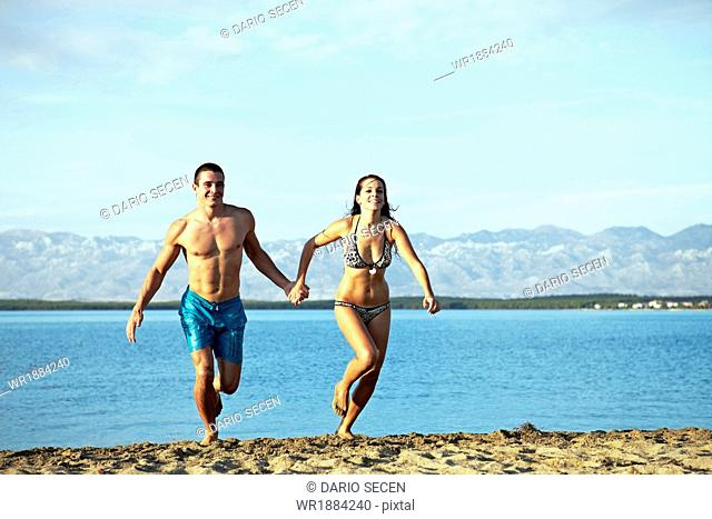 Young couple running on beach