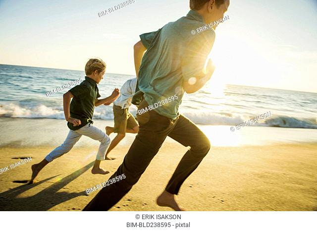 Caucasian brothers running on beach