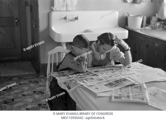 Children reading Sunday papers, Rustan brothers' farm near Dickens, Iowa. Note convenience of running water in background