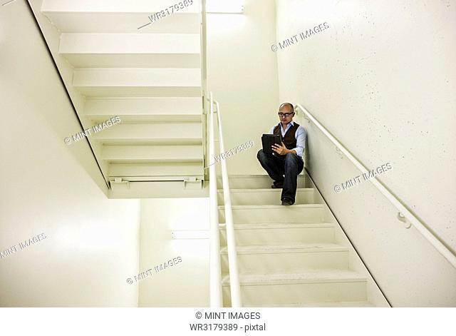 Asian businessman sitting in a stairwell working on a notebook computer