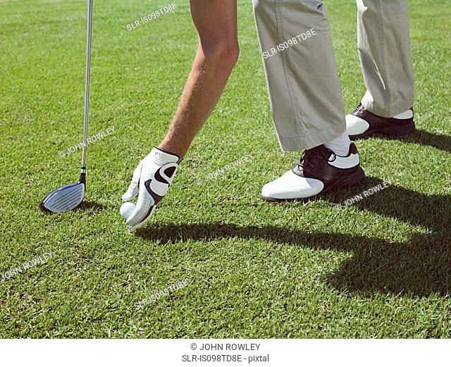 Man playing golf, picking up ball