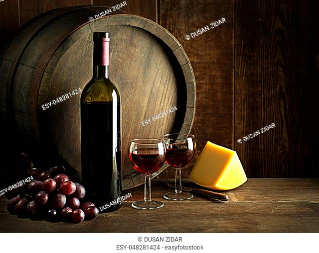 Bottle of red wine with glasses and cheese on wooden and barrel background