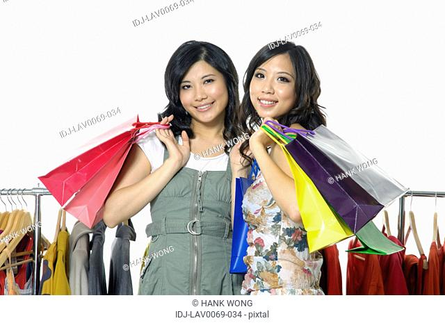 Women carrying shopping bags and smiling