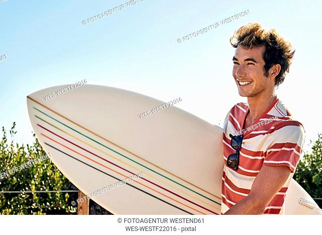 Smiling young man carrying surfboard