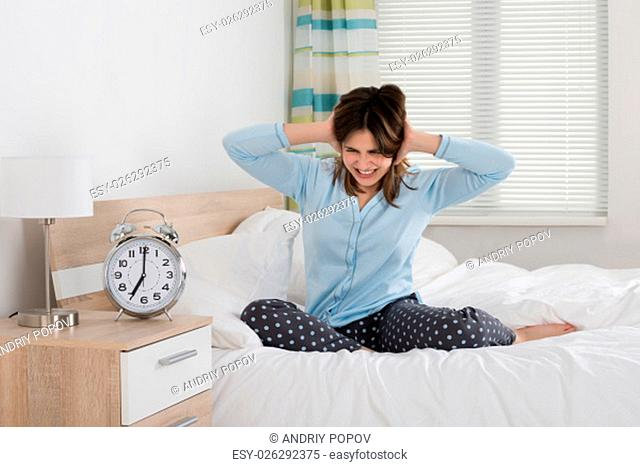 Exhausted Young Woman Awakened By An Alarm Clock In Her Bedroom