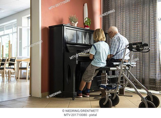 Grandfather teaching piano instrument to his grandson
