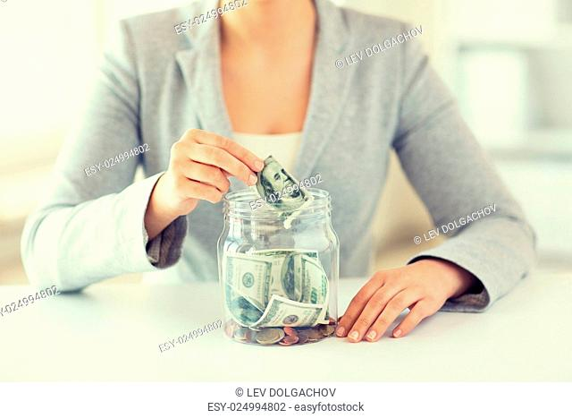 business, finance, saving, banking and people concept - close up of woman hands putting us dollar money into glass mason jar
