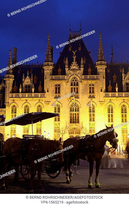 Provinciaal Hof and horse-drawn carriages, illuminated at night, Bruges, Belgium