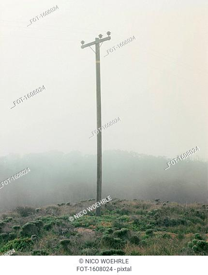 Electricity pylon on hill in foggy weather