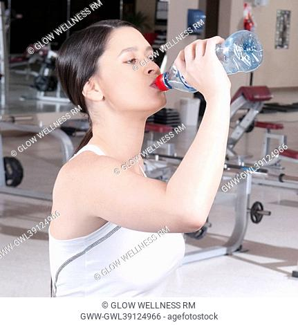 Close-up of a woman drinking water in a gym